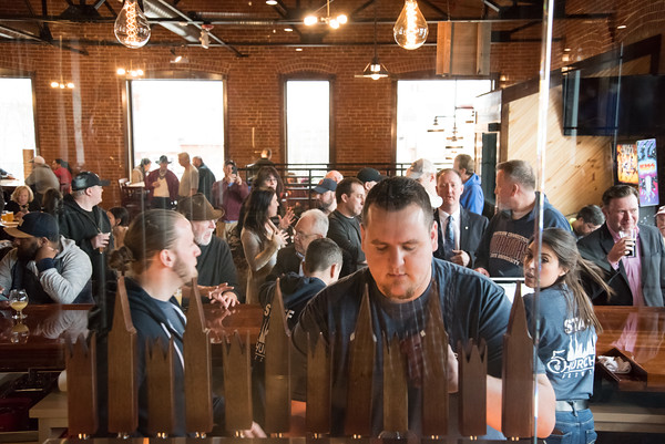 03/30/18 Wesley Bunnell   Staff 5 Churches Brewing held their ribbon cutting with city officials on Friday at noon to a crowd of customers lined down the sidewalk. Jake Lounsbury pours a beer for customer as the packed crowd can be seen in the background.
