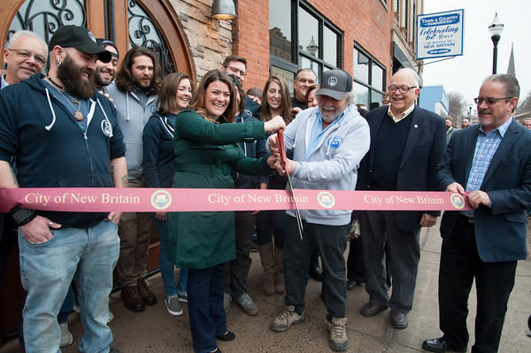 03/30/18 Wesley Bunnell | Staff 5 Churches Brewing held their ribbon cutting with city officials on Friday at noon to a crowd of customers lined down the sidewalk. From L Economic Development Director Bill Carroll, co-owner Andrew Lemnotis, co-owner Mike Barillaro, brewer Austin Japs, co-owner Christina Caccioppoli co-owner Phil Lemnotis, Becca Lemnotis co-owner Andrew Sklavouris, Alderman Don Naples, President of the New Britain Chamber of Commerce Tim Stewart and in front Mayor Erin Stewart current the ribbon with co-owner Peter Lemnotis,