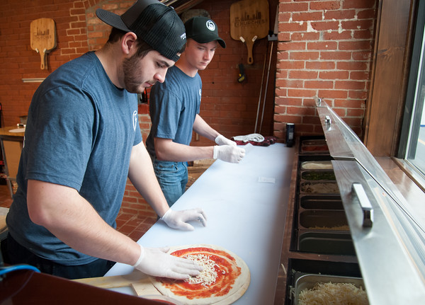 03/30/18 Wesley Bunnell   Staff 5 Churches Brewing held their ribbon cutting with city officials on Friday at noon to a crowd of customers lined down the sidewalk. Jacob Larche prepares a pizza as James Cox, rear, waits to place it in the brick oven.