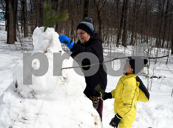 3/8/2018 Mike Orazzi | Staff Melissa Matthews and her son Myles, turning 9 this Saturday, while working on a snowman in Bristol's Rockwell Park Thursday morning.