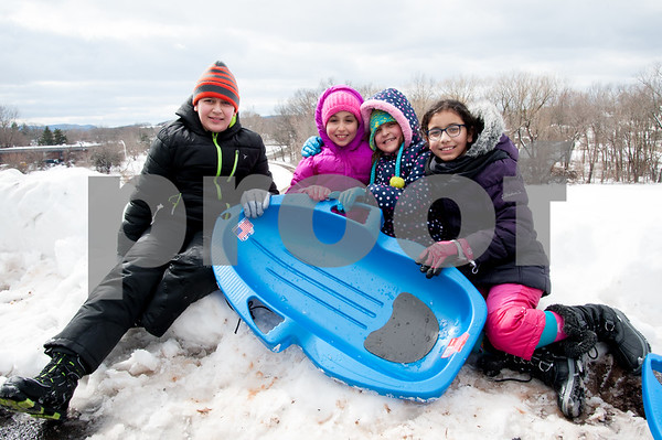 03/08/18 Wesley Bunnell | Staff Taking a break from sledding are Mohammed Essaqui, age 13, Nora Boumargoud, age 7, Fatima Essaqui, age 9, and Aya Amekzaz, age 10. The group was sledding at Smith Elementary School on Thursday following heavy snow through the city on Wednesday afternoon through the night.