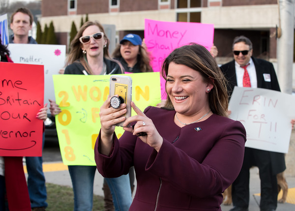 04/04/18 Wesley Bunnell | Staff New Britain Mayor Erin Stewart uses her phone to hold a Facebook Live chat outside of New Britain High School before the CT GOP held their 4th gubernatorial debate of the season as supporters hold signs and chant in her support. Mayor Stewart was unable to speak at the event for not reaching the minimum funds required to participate.
