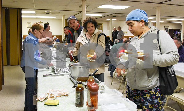 050917 Wesley Bunnell | Staff New Britain's homeless are invited to St. Peter's Church on Tuesday evening for a free meal served by volunteers. Volunteer Jo Deccy, left, helps serve.