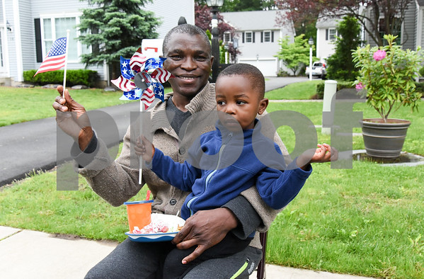052917 Wesley Bunnell | Staff Plainville held their annual Memorial Day Parade on Monday morning followed by a memorial unveiling dedicated to Gold Star Families at Veterans Memorial Park. Samuel Adedimeji , age 2, sits on his father Adebola Adedimeji's lap as they watch the parade pass.