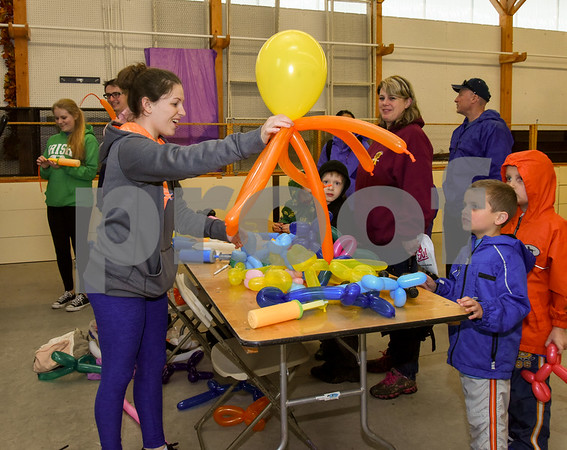 052517 Wesley Bunnell | Staff The Berlin High School Upbeat Club held their annual picnic at the Berlin Fair Grounds on a soggy Thursday May 25. Senior Cara Gileau makes an octopus balloon animal for six year old Tony Pietraoia.