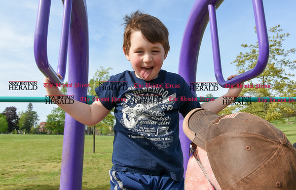 051617 Wesley Bunnell   Staff Six year old Brody Barnes sticks his tongue out as he does pull ups in Walnut Hill Park on Tuesday afternoon with a little help from his father Matt Burns.