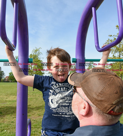 051617 Wesley Bunnell | Staff Six year old Brody Barnes sticks his tongue out as he does pull ups in Walnut Hill Park on Tuesday afternoon with a little help from his father Matt Burns.