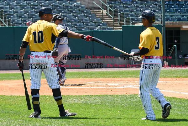 051617 Wesley Bunnell | Staff The New Britain Bees vs the Bridgeport Bluefish in the 2nd game of a double header played early afternoon on Tuesday. Mike Crouse (10) hands the bat back to James Skelton (3) after his at bat.