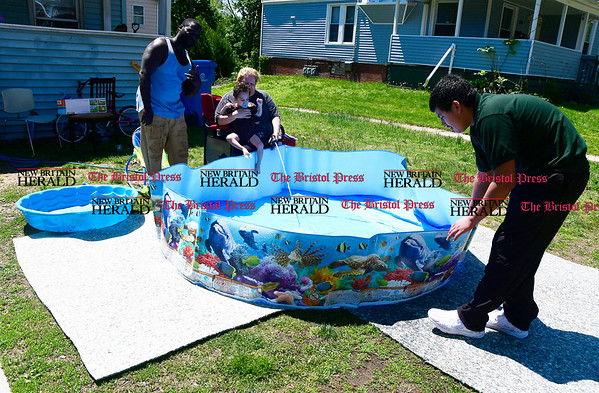 5/17/2017 Mike Orazzi | Staff Ivin Williams, Jayden Gonzalez, Lydia Marselle and Carmelo Aldarondo fill a couple of swimming pools on High Street in Bristol while preparing to beat the heat Wednesday.