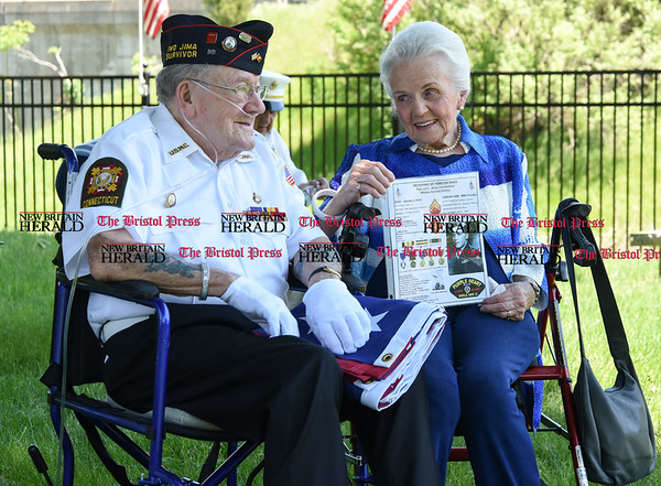 051817 Wesley Bunnell | Staff 95 year-old Iwo Jima survivor George Caron sits next to his wife Lois as she holds a handout covering George's WWII accomplishments. The Caron's purchased a custom made 48 star flag to replace the worn flag that was being used at the memorial.