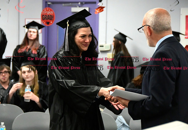 5/18/2017 Mike Orazzi | Staff Rosa Martinez-Farias receives her diploma from Adult Education Director Larry Covino during Thursday night's graduation ceremony.