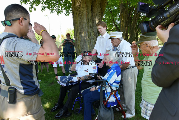 051817 Wesley Bunnell | Staff Newington firefighter David Sanabria, L, salutes 95 year-old Iwo Jima Survivor George Caron, middle, during a flag changing ceremony at the Iwo Jima Memorial on Thursday afternoon. George along with his wife Lois, 3rd from L, purchased a custom made 48 star flag to replace the worn flag that was being used. WWII Navy veteran Peter Spano stands behind Lois.