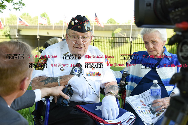 051817 Wesley Bunnell | Staff 95 year-old Iwo Jima survivor George Caron sits with his wife Lois while being interviewed by a television reporter. The Caron's purchased a custom made 48 star flag to replace the worn flag being used at the Iwo Jima Memorial.