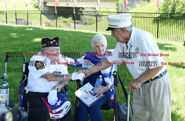 051817 Wesley Bunnell | Staff WWII Marine veteran and Iwo Jima survivor George Caron, L, shakes hands with WWII Navy Veteran Peter Spano during a ceremony to replace the worn flag at the Iwo Jima Memorial. George Caron along with his wife Lois purchased a custom made 48 star flag to replace the worn flag.