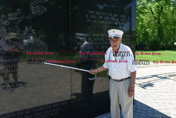 051817 Wesley Bunnell | Staff WWII Navy veteran Peter Spano examines the marble base at the Iwo Jima Memorial on Thursday afternoon. 95 year-old Iwo Jima survivor George Caron along with his wife Lois purchased a custom made 48 star flag to replace the worn flag being used at the Iwo Jima Memorial.
