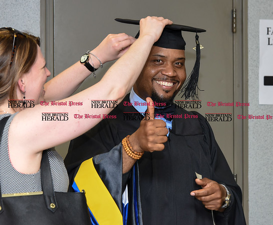 051817 Wesley Bunnell | Staff CCSU held commencement exercises on Thursday evening for graduate students at Kaiser Hall. Kevin Booker Jr. receives help with his cap before the start of the ceremony.