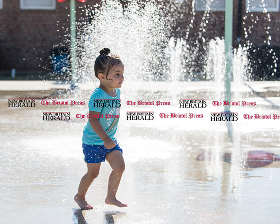 070516 Wesley Bunnell | Staff Savannah Sturgeon of New Britain cools down with a trip to the splash pad with her father Scott on Tuesday afternoon.