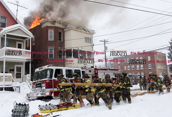 020917 Wesley Bunnell | Staff A multi family home at 116 West St. in New Britain was heavily damaged in a fire on Thursday Feb 9 with 10 people needed to be rescued from the burning building. Firefighters work together to move a hose out of the way for an additional ladder truck to move into position.