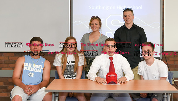 051917 Wesley Bunnell | Staff Southington High School wrestler Austin Abacherli sits with friends after signing his letter of intent to wrestle for Sacred Heart University.