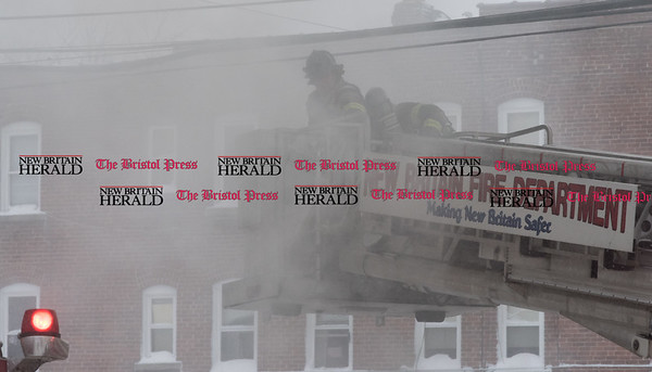 020917 Wesley Bunnell | Staff A multi family home at 116 West St. in New Britain was heavily damaged in a fire on Thursday Feb 9 with 10 people needed to be rescued from the burning building. Heavy smoke partially obscures a firefighter from Ladder 2 as it moves into position.