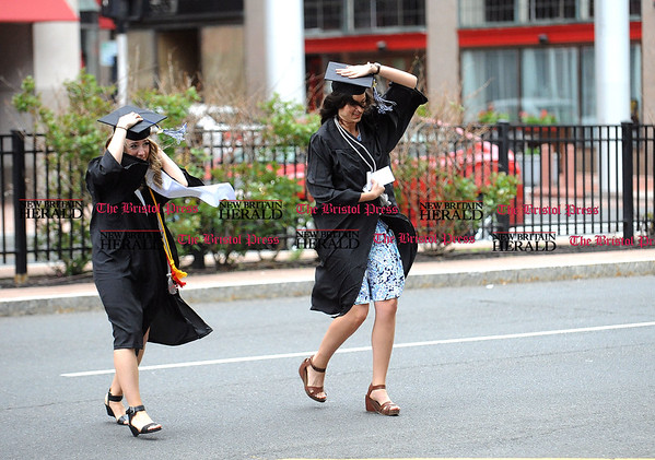 5/20/2017 Mike Orazzi   Staff Olivia McDonald and Katherine Diehl hold their caps as the run across a windy Trumbull Street toward the XL Center in Hartford for CCSU's graduation Saturday morning.