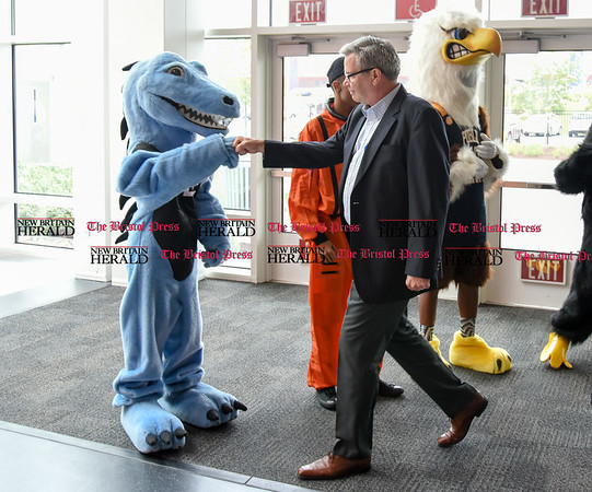 052217 Wesley Bunnell | Staff Energy company Dynegy visited CREC Academy of Science & Innovation to present a donation for $100,000 for CREC athletics. Dynegy Executive V.P. of Operations Marty Daley high fives the MLC Blue Dragon mascot.