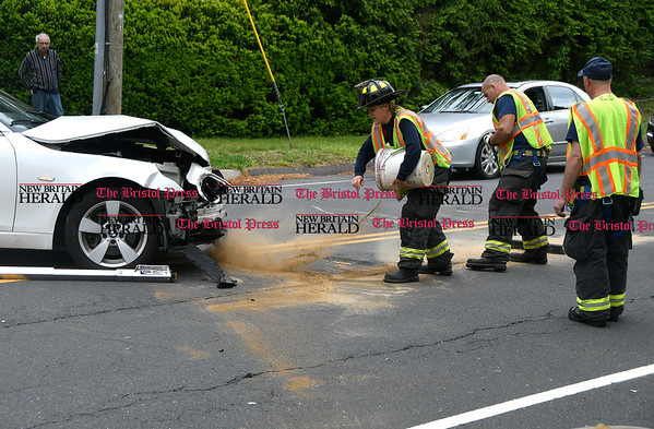 5/26/2017 Mike Orazzi | Staff Bristol firefighters spread sand at the scene of a two car crash at the intersection of Stafford Avenue and Sonstrom Road Friday afternoon. Both cars were towed from the scene and a child was evaluated by EMS.