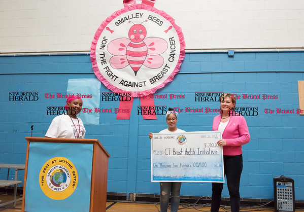 052617 Wesley Bunnell | Staff Smalley Academy presented the CT Breast Health Initiative with a check for over $2,000 through various fund raising activities. Smalley Say No to Breast Cancer committee member Paula Richardson stands at the podium as a Smalley student presents CT Breast Health Initiative Presdient Joyce Bray with a ceremonial check.