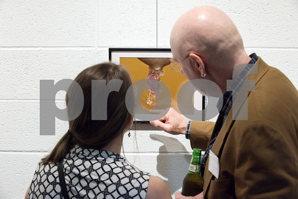 053117 Wesley Bunnell | Staff Artist Craig Frederick points to a photograph at the opening of artist Mika Glogowski's show Photographic Abstractions: The Unseen Works by Mika Glogowski. Frederick has mentored Glogowski as part of his initiative to mentor young professionals.