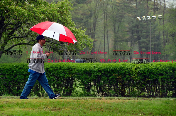 5/5/2017 Mike Orazzi | Staff Kewin Morales walks along King Street in Bristol during Friday's rain.
