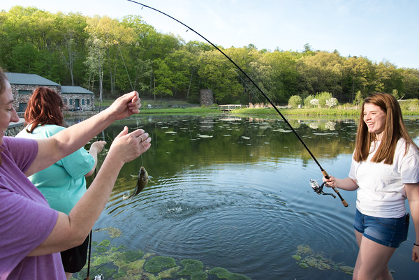 05/14/18 Wesley Bunnell | Staff Miranda Hoadley, L, helps take the sunfish from her daughter Kira's fishing line while fishing at Rockwell Park on Monday evening.