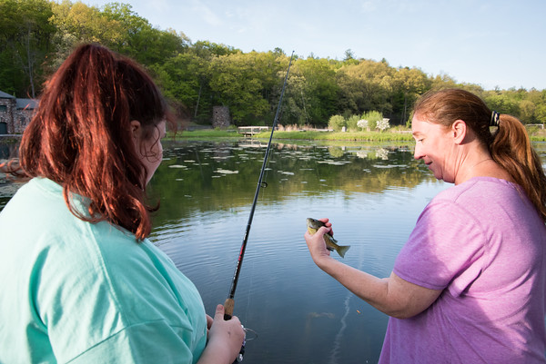 05/14/18 Wesley Bunnell | Staff Makenna Hoadley, L, has mom Miranda help take the sunfish from her line while fishing at Rockwell Park on Monday evening.