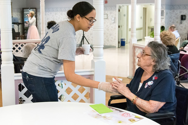 05/15/18 Wesley Bunnell | Staff Singer Kate Stone entertained the residents of Autumn Lake Healthcare in New Britain during Happy Hour on Wednesday May 15th. A worker hands a drink to Theresa Ciaffaglione during the performance.