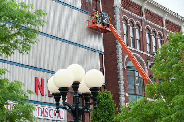 05/16/18 Wesley Bunnell | Staff Workers remove the corrugated metal covering from the front of 222 Main St near Central Park on Wednesday afternoon to reveal the original brickwork from its 1885 construction.