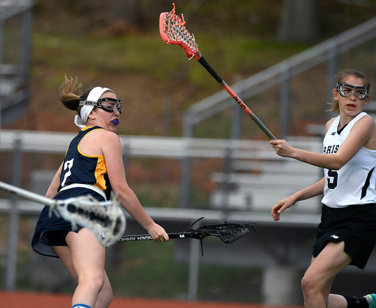 5/8/2018 Mike Orazzi | Staff RHAM's Jules Turo (7) and Bristol Co-Op Lacrosse's Allison Jessie (5) during girls lacrosse at BEHS Tuesday.