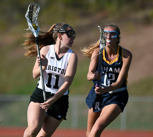 5/8/2018 Mike Orazzi | Staff Bristol Co-Op Lacrosse's Ashley Macdonald (11) and RHAM's Shannon Romeo (12) during girls lacrosse at BEHS Tuesday.