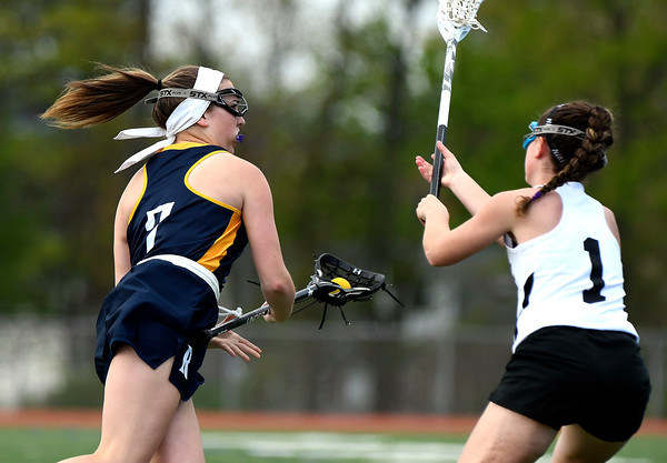 5/8/2018 Mike Orazzi | Staff RHAM's Jules Turo (7) Bristol Co-Op Lacrosse's Jenna Lowe (1) during girls lacrosse at BEHS Tuesday.