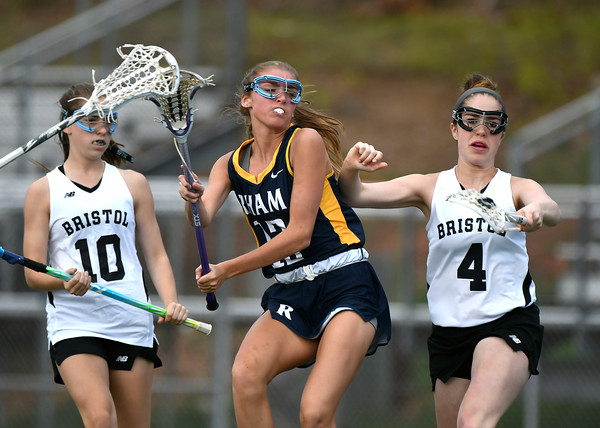 5/8/2018 Mike Orazzi | Staff RHAM's Shannon Romeo (12) and Bristol Co-Op Lacrosse's Lily Hansen (10) and Erika Santilli (4) during girls lacrosse at BEHS Tuesday.