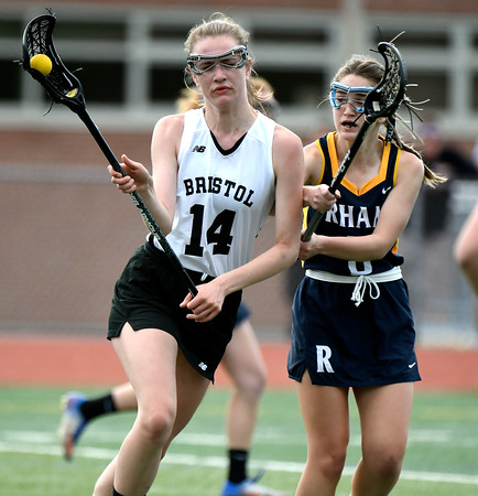 5/8/2018 Mike Orazzi | Staff Bristol Co-Op Lacrosse's Ashley Watson (14) and RHAM's Mia Rhodes (3) during girls lacrosse at BEHS Tuesday.