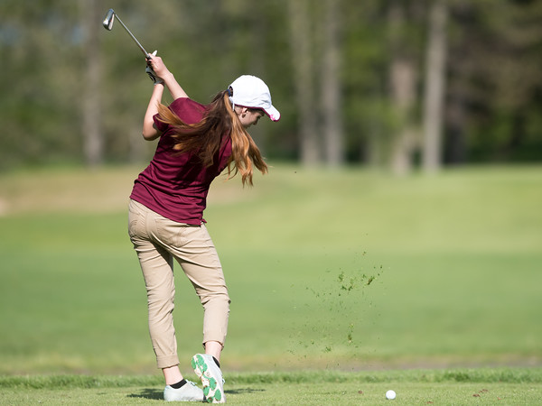05/09/18 Wesley Bunnell | Staff Berlin girls golf vs New Britain on Wednesday afternoon at Timberlin Golf Course in Berlin. Grass flies as New Britain's Kiley Griffin takes a practice swing.