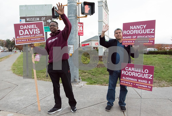11/6/17 Wesley Bunnell | Staff Alderman Daniel Davis, L, and Alderman Carmelo Rodriguez wave to motorists on the corner of West Main & Corbin Ave on Monday afternoon ahead of Tuesday's elections.