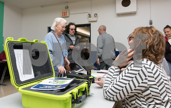 11/7/17 Wesley Bunnell | Staff Genevieve Wantek, L, is check in by Official Checkers Beverly Dube and Ron Field using the new Poll Pad verification system at Slade Middle School on Tuesday morning.