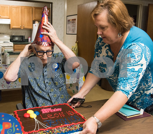 11/14/17 Wesley Bunnell | Staff Jerry DeVito, age 100, celebrated his birthday along with Leon Hatoff, age 104, at Franklin Square Manor on Tuesday afternoon. DeVito puts on a birthday hat as Property manager Bonny Boehnert slides the cake onto the table.