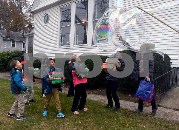 11/14/2017 Mike Orazzi | Staff Giant bubbles make by Pastor Bryce Whiting at the Calvary Advent Church in Bristol Tuesday afternoon. The pastor treated children from the Immanuel Lutheran School to bubbles as they dropped off boxes of donated items for Operation Christmas Child.