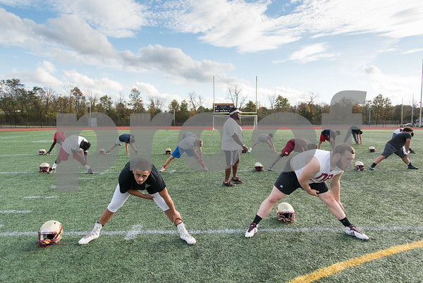 11/2/17 Wesley Bunnell | Staff New Britain high school football held a walk through practice without pads on Thursday afternoon at Veterans' Stadium. Coach Cluewi Challenger , middle, leads the team through stretches. Jacob Clark (54), R.