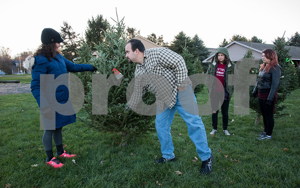 11/24/17 Wesley Bunnell | Staff Brooke Barbero, L, and Dennis DeCesare discuss potential Christmas tree's at the Kiwanis of Berlin tree sale at Massirio Drive on Friday afternoon as Nicole and Alyssa Vasil look on.