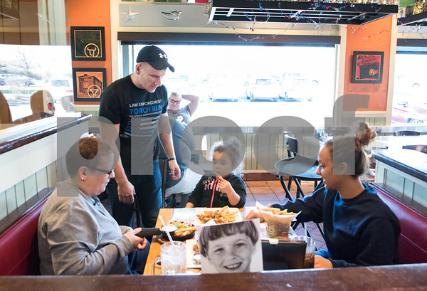 11/24/17 Wesley Bunnell | Staff New Britain Police held their Tip A Cop event to benefit the CT Special Olympics on Friday at Chili's in New Britain. Two year old Nylah Serrano blows on her french fry to cool it down after being served by Ofc. Lonczak as Carmen Santiago, L, and Edalys Batista look on.