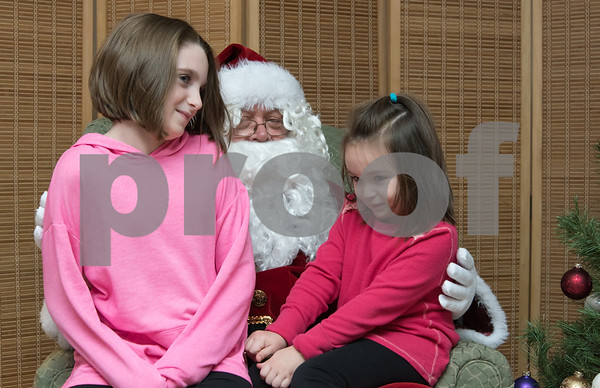 11/27/17 Wesley Bunnell | Staff Santa and Mrs. Claus visited the Berlin Recreation Center on Monday evening as guests from Berlin Parks & Recreation. Mya Kelly, age 9, and Ava Kelly, age 4, sit on Santa's lap and give their Christmas list.
