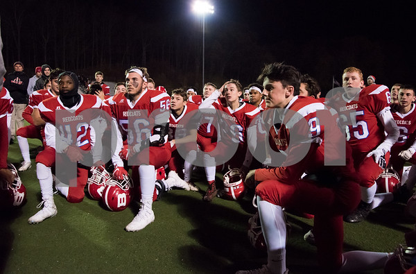 11/28/17 Wesley Bunnell | Staff Berlin football defeated Watertown in a playoff game on Tuesday night at Sage Park in Berlin. Players take a knee as they listen to head coach Joe Aresimowicz. Tyler Dinkins (42), Dominic Lattarulo (56) and Kevin Dunn (9).