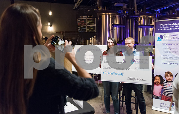 11/28/17 Wesley Bunnell | Staff The Community Foundation of Greater New Britain held a Giving Brewsday event at Alvarium Beer on Tuesday evening for young entrepreneurs to become involved in the foundation. Office Manager and Scholarship Associate Kim Duncan, L, takes a photos of Shelby and Chris Anderson after the pair made a donation to the foundation.